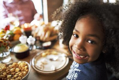 Young girl smiling at Thanksgiving Table