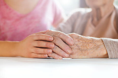 Caregiver holding elderly's hand